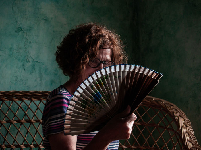 Portrait Of Woman Holding Hand Fan While Sitting On Seat At Home