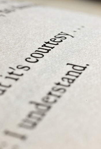 """The sentence """" courtesy """"on a book page , studio shot , macro photography Letters Macro Photography Text Book Close-up Communication Conceptual Courtesy Diagonal Lines Education Fantasy Font Idea Info Ink Language Literature No People Page Paper Phrase Selective Focus Sentence Text Words"""