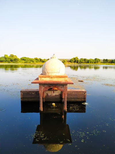 Built structure in lake against clear sky