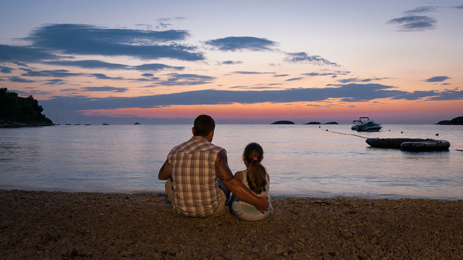 Father and daughter sitting on shore at beach against sky during sunset