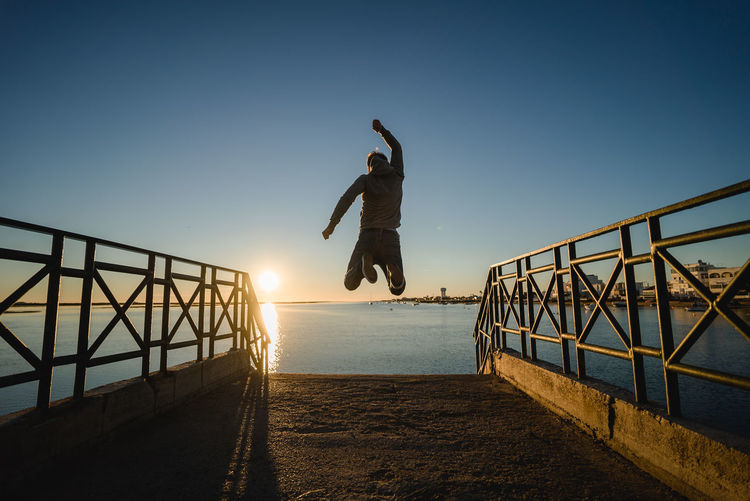 Man Jumping Over Pier At Beach Against Sky