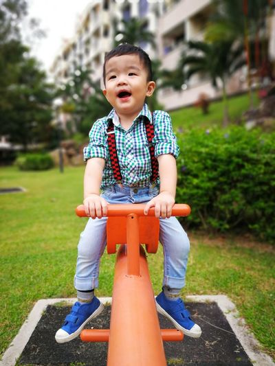 Full length of cute baby boy sitting on seesaw at playground