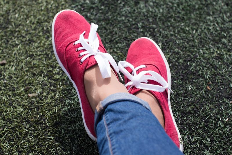Young woman's feet in red sport shoes on grass field Tired Lazy Sportwear Leisure Activity Summer Recreation  Relaxing Sport Football Field Grass Field Shoe Human Leg Low Section Personal Perspective High Angle View Lifestyles Casual Clothing Human Foot Day