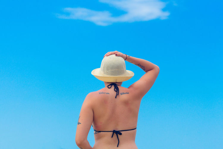 Rear view of bikini woman wearing hat against blue sky