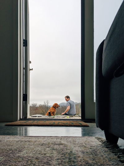 Rear view of man with dog sitting outdoors