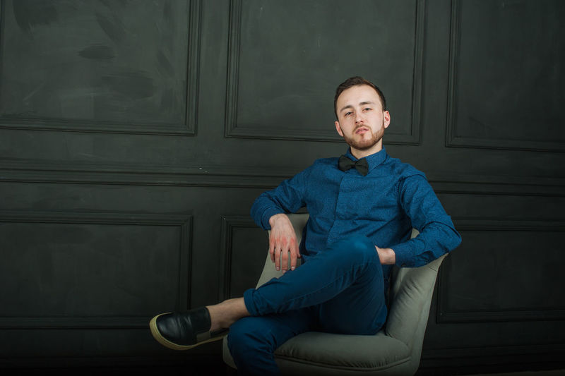 Portrait of young man sitting on chair by wall