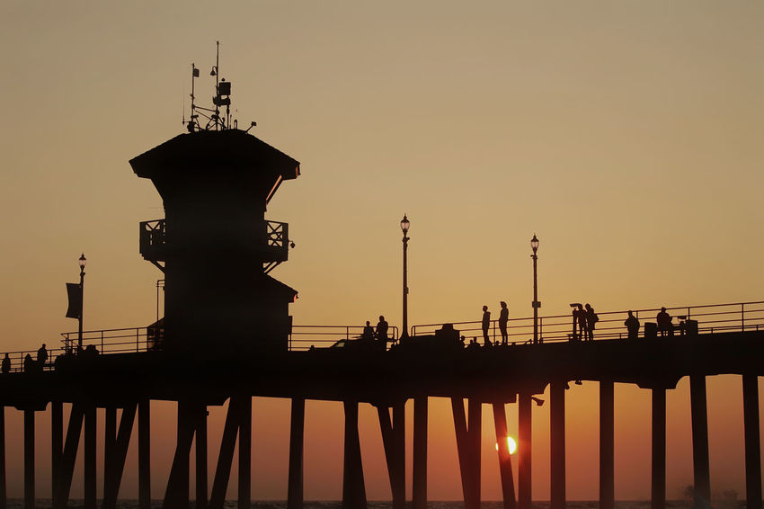 evening mood Huntington Beach Pier Silhouettes Sunset Silhouettes The Week On EyeEm Architecture Beauty In Nature Building Exterior Built Structure Clear Sky Incidental People Nature Outdoors Pentax People Sea Silhouette Silhoutte Photography Sky Sunset Water