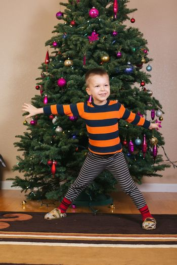Smiling boy with arms outstretched standing against christmas tree at home
