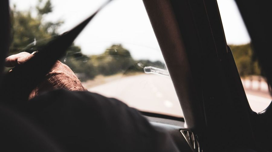 Cropped Hand Of Man Smoking Cigarette In Car