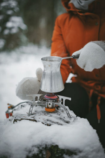 Midsection of woman making drink on camping stove during winter