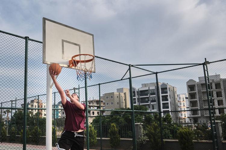 Man playing basketball hoop against sky in city