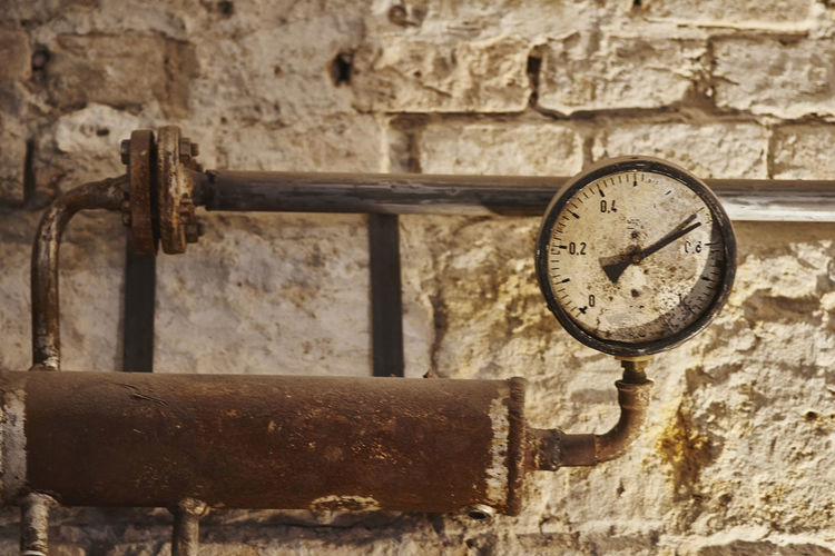 Close-Up Of Gauge On Old Distiller Against Wall