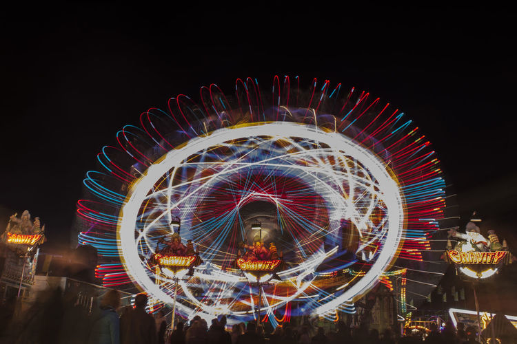 Low angle view of people by illuminated amusement park rides against sky at night