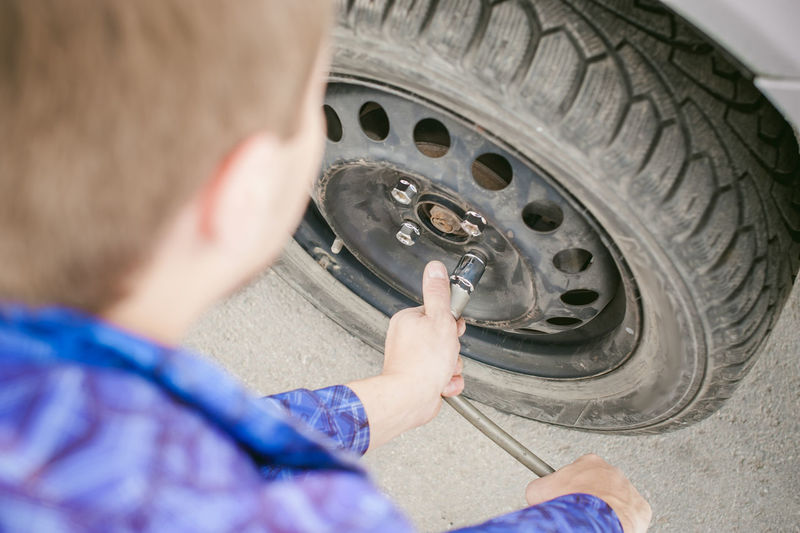 Cropped Image Of Mechanic Fixing Car Tire
