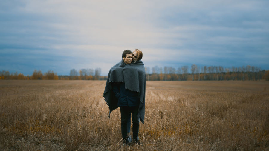 Couple Wrapped In Blanket On Field Against Cloudy Sky
