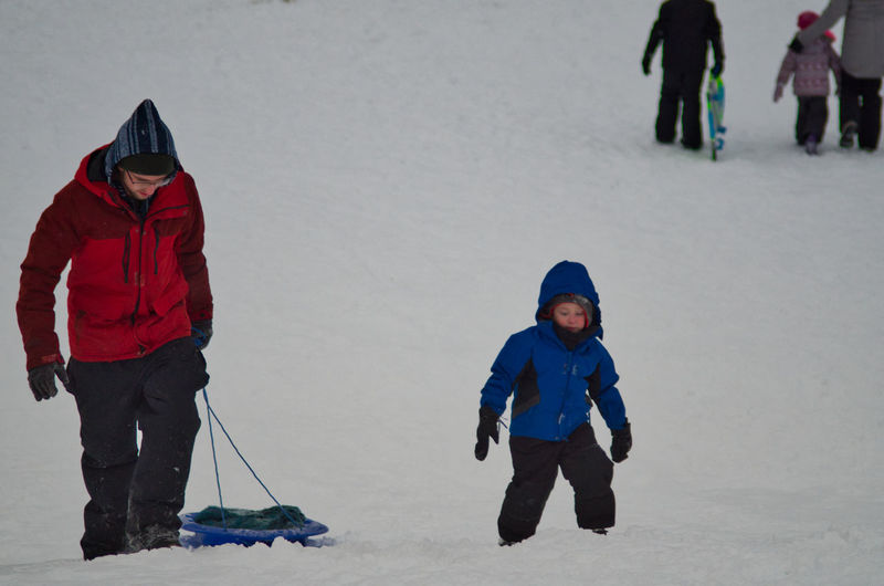 Father and son walking on snow covered land