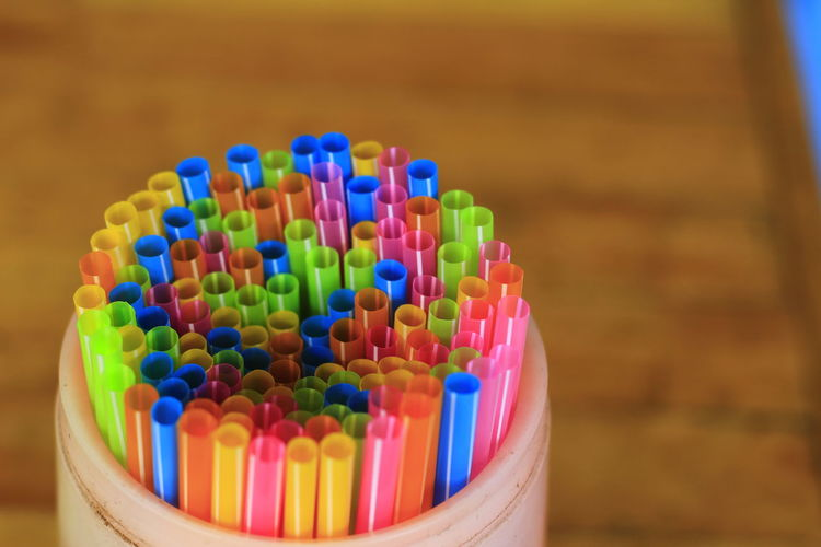 Close-up of multi colored drinking straws in container