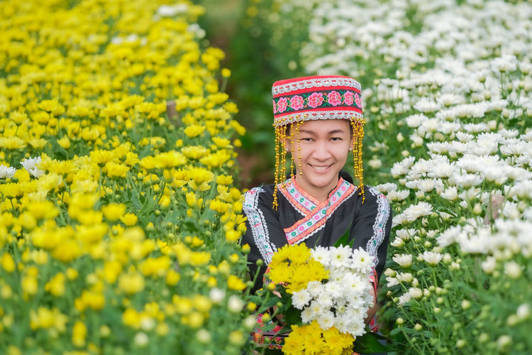 Portrait of smiling woman wearing traditional clothing standing amidst flowering plants