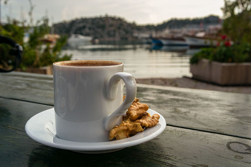A white china cup of Turkish coffee dressed with a side of walnuts on a table top to the back drop of a Med sea harbour in Turkey. Coffee Coffee - Drink Coffee Cup Crockery Cup Day Drink Focus On Foreground Food Food And Drink Freshness Hot Drink Mug No People Outdoors Ready-to-eat Refreshment Saucer Snack Still Life Table Temptation Walnuts Wood - Material