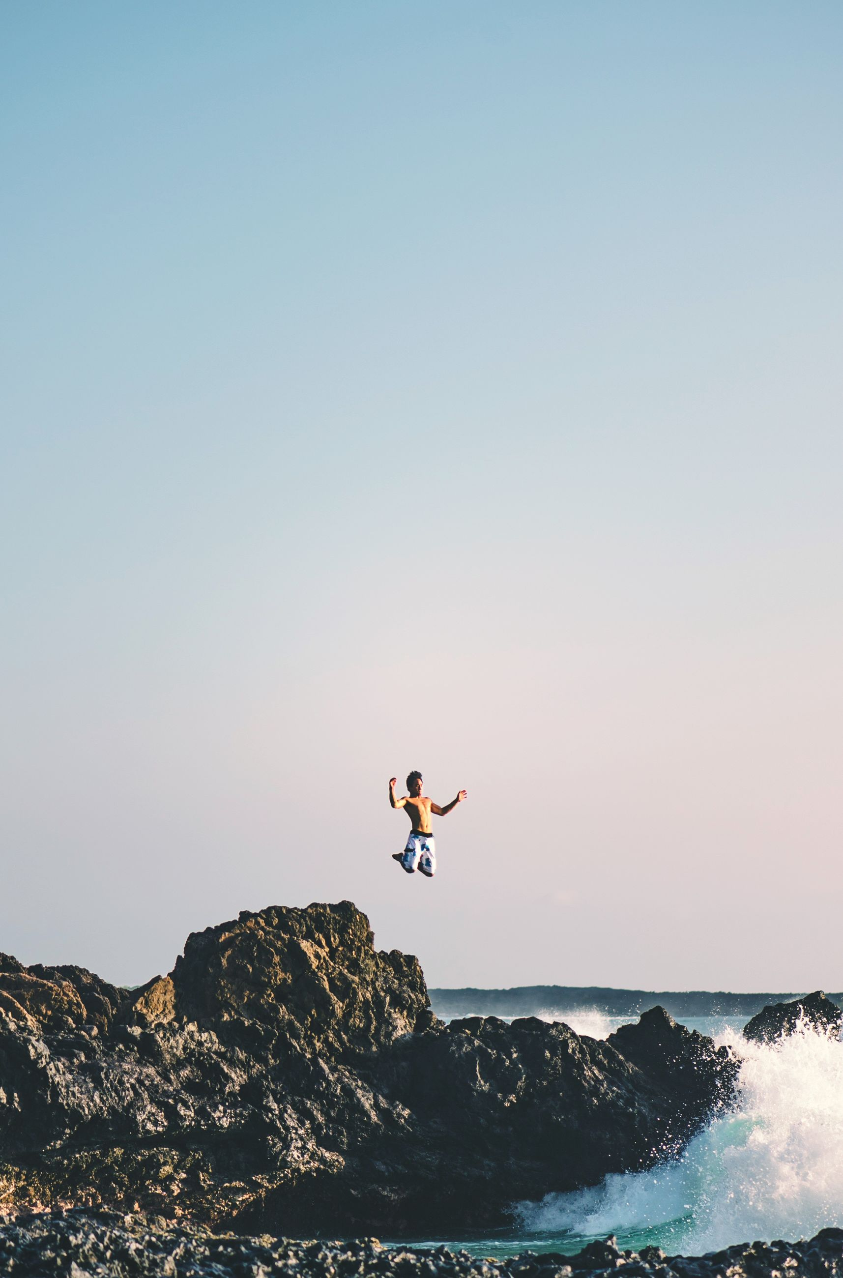 sea, clear sky, flying, mid-air, water, copy space, adventure, extreme sports, scenics, horizon over water, nature, beauty in nature, full length, tranquil scene, tranquility, rock - object, leisure activity, motion