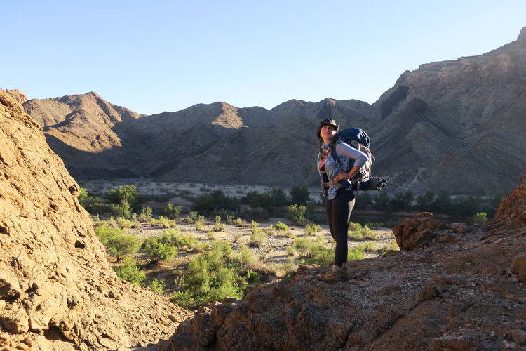 Female hiker standing on top of hill overlooking scenic valley Adventure Backpack Bag Beauty In Nature Explore Hike Hiker Hiking Landscape Landscape_Collection Let's Go. Together. Mountain Mountain Range Namibia Nature One Person Outdoor Photography Outdoors Rock - Object Rocky Mountains Standing Sunlight Young Adult