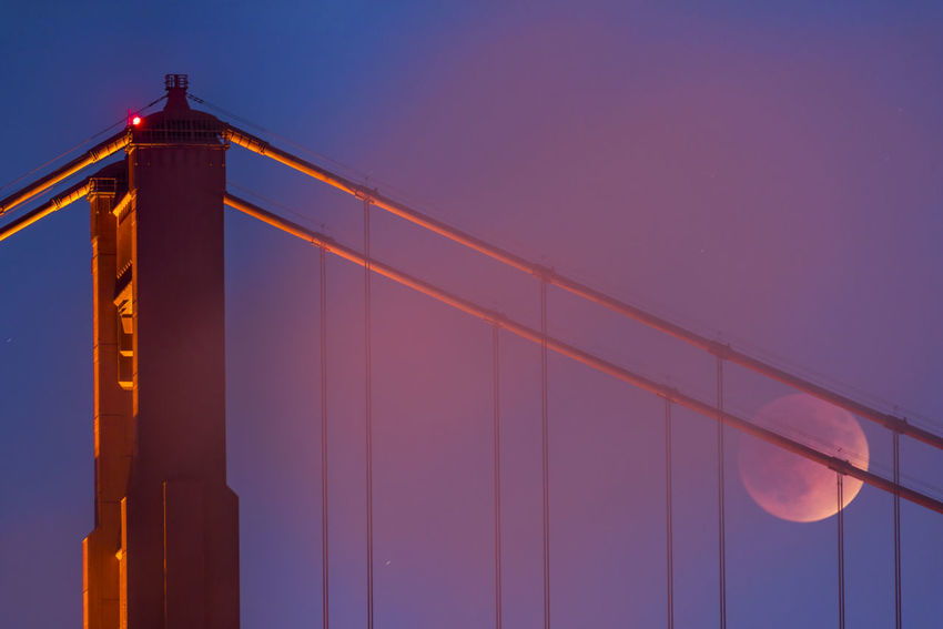 Eclipse moon rises behind the Golden Gate bridge at dusk as a layer of fog adds a misty look to the center of the image with the reddish moon behind the cables. Golden Gate Bridge Moon Eclipse Lunar Eclipse San Francisco California Suspension Bridge Transportation Architecture Sky Dusk Nature Travel City Tourism Illuminated Bridge Travel Destinations Outdoors Sunset City Lights Built Structure