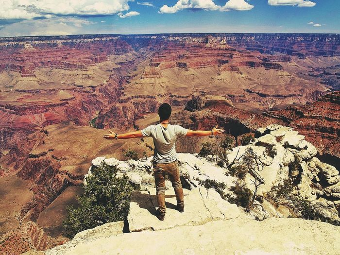 Full Length Rear View Of Man Standing On Rock With Arms Outstretched At Grand Canyon National Park