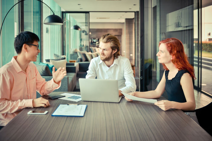 Brainstorming Discussing Adult Business Business People Business Person Businessman Businesswear Businesswoman Colleague Colleagues Communication Cooperation Coworker Day Group Indoors  Meeting Meeting Room Multi Ethnic Occupation Office Sitting Table Teamwork Technology Using Laptop Western Wireless Technology Women Working Young Adult Young Women