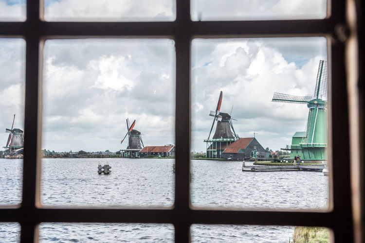 Traditional windmills by river seen through window