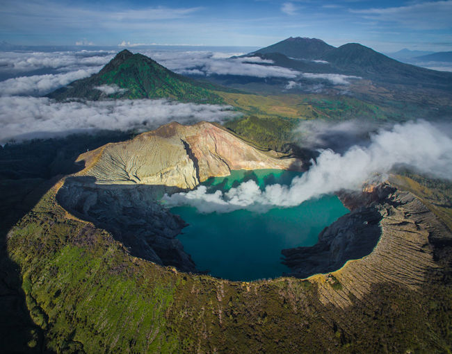 An Aerial Drone View of Kawah Ijen - Early in the Morning. The Ijen volcano complex is a group of composite volcanoes in the Banyuwangi Regency of East Java, Indonesia. Beautiful INDONESIA Active Volcano Banyuwangi Beauty In Nature Cloud - Sky Environment Geology Ijen Indonesia_photography Kawah Ijen Kawahijen Landscape Mountain Mountain Peak Nature No People Physical Geography Power In Nature Scenics - Nature Sky Smoke - Physical Structure Volcanic Crater Volcanic Landscape Volcano Go Higher