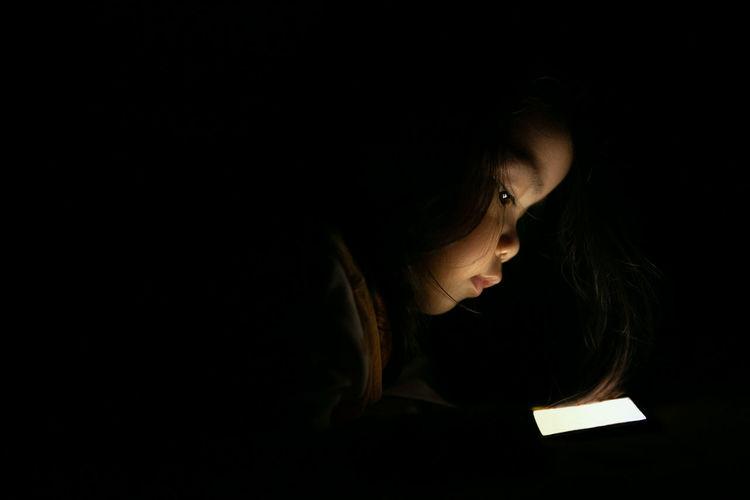 Close-up of toddler using mobile phone in dark