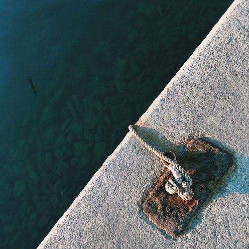 High angle view of rope tied to cleat on pier