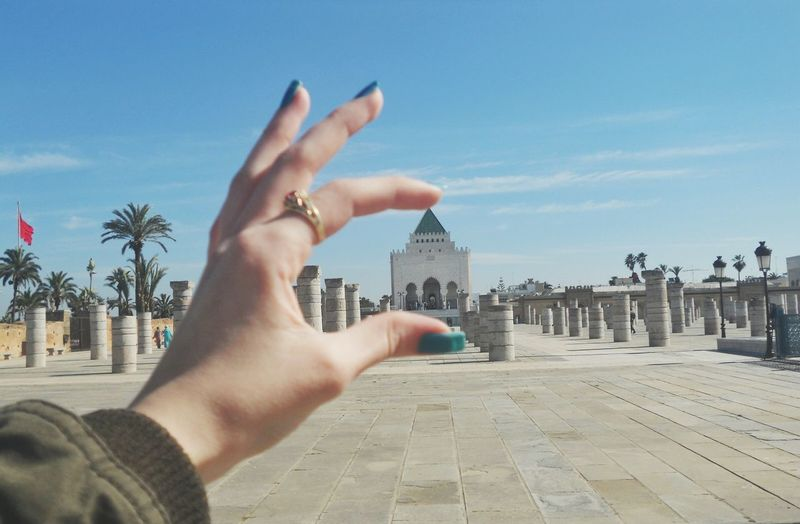 Optical Illusion Of Woman Holding Hassan Tower Against Blue Sky