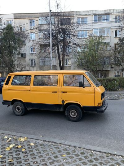 Yellow car on street against buildings in city