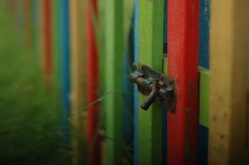 Close-Up Of Latch Of Multi Colored Fence