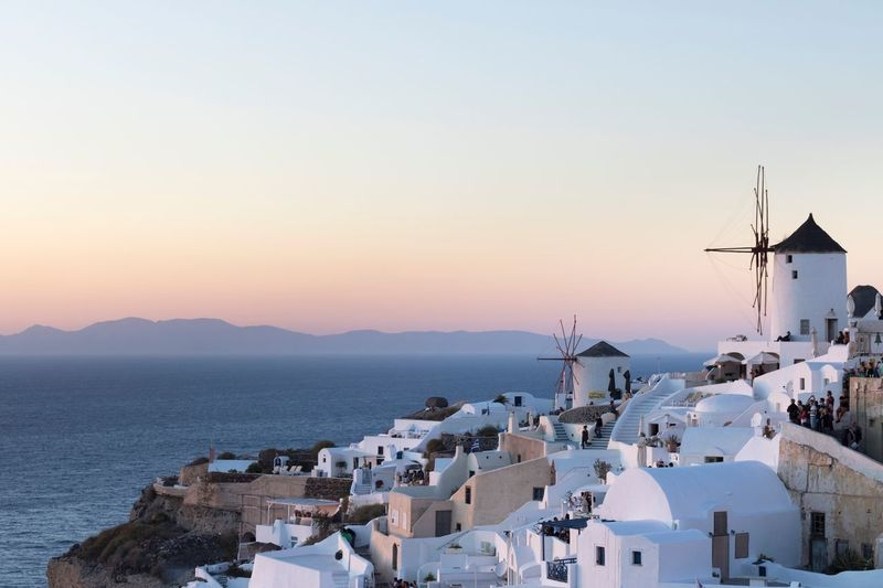 Betterlandscapes Architecture Sea Water Sunset Nature City Sky Windmill Outdoors White Island Cityscape Greece Santorini Renewable Energy Oia Colorful Sky Beauty In Nature White And Blue White Building Built Structure EyeEm Selects Lost In The Landscape