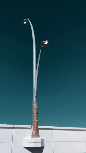 Close-up of electric lamp against blue sky
