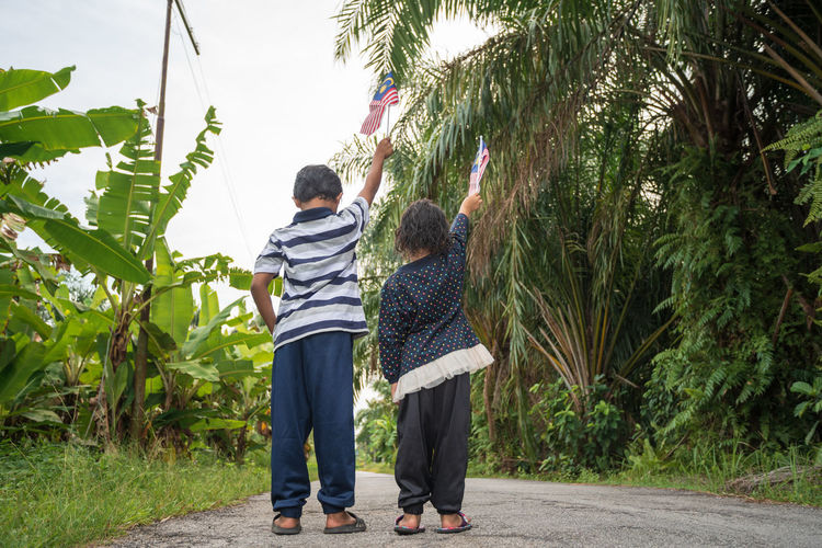 Rear View Siblings Holding Malaysian Flag While Standing On Road Amidst Plants