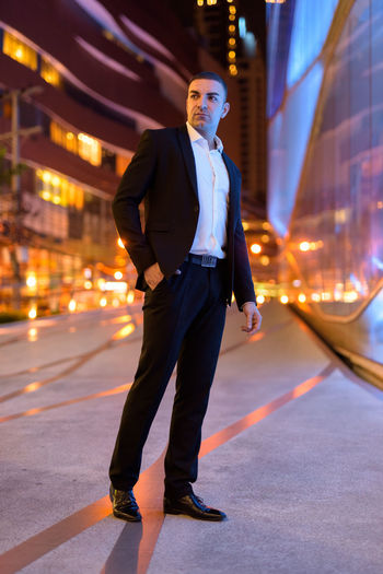 Full length of businessman standing on road at night