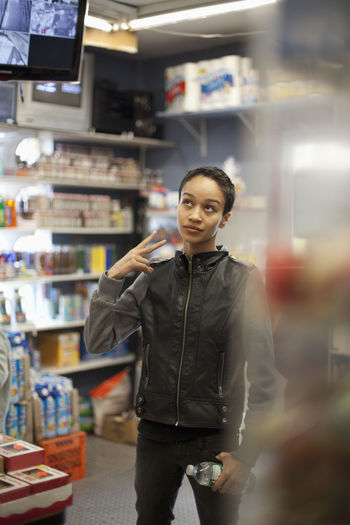 Portrait of young woman standing in store