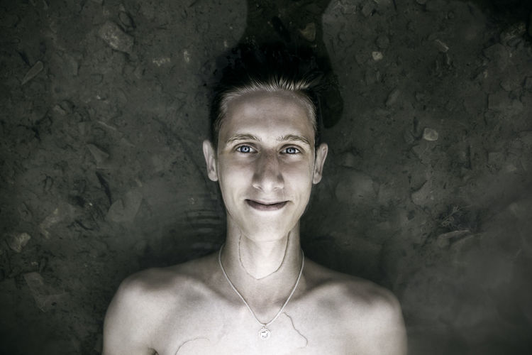 Portrait Of Shirtless Young Man Lying Down In Water