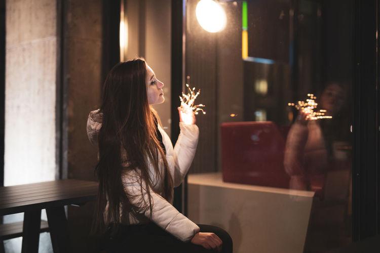 Woman Holding Illuminated Lighting Equipment While Sitting At Restaurant
