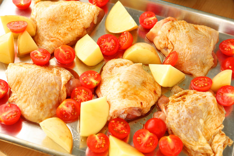 Chicken thighs dinner with Yukon gold potatoes Home Cooking Homemade Food Natural Light Poultry Textures Balanced Meal Cherry Tomatoes Chicken Thighs Closeup Food Food Preparation Healthy Eating Indoors  Meat No People One Pan Meal Potatoes Raw Food Savory Food Sheet Pan Dinner Studio Shot Uncooked Vegetables