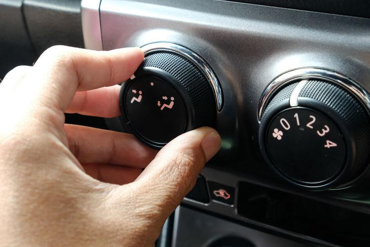 Close-up of hand adjusting knob in car