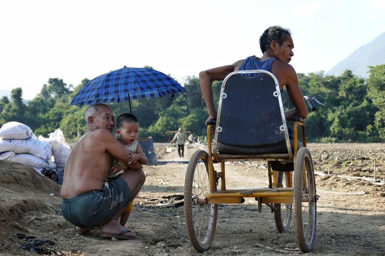Vang Vieng Laos Rural People People Watching Sitting Togetherness Father And Son Weelchair Travel Traveling Streetphotography Outdoors Umbrella Connected By Travel An Eye For Travel