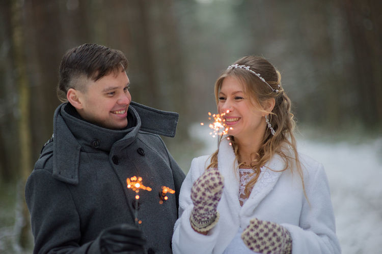Happy Couple With Sparklers Looking Face To Face During Winter