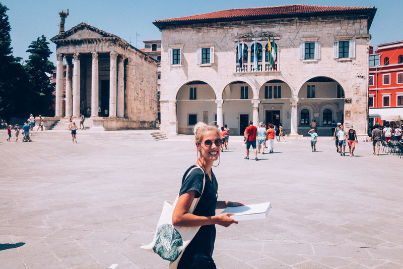 Portrait Of Smiling Young Woman Standing Against Buildings At Town Square