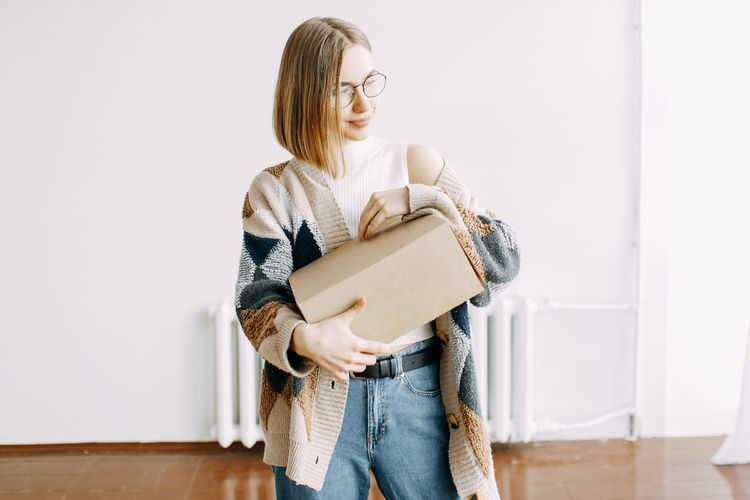 A girl receives a parcel from a courier, delivery, order, box, online shopping, millennial, hipster,