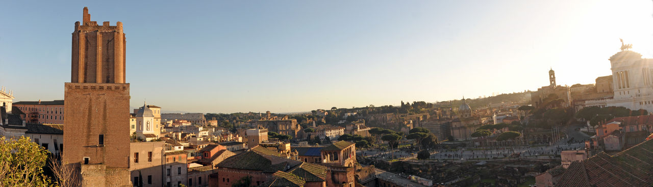 Panoramic view of buildings in town against clear sky