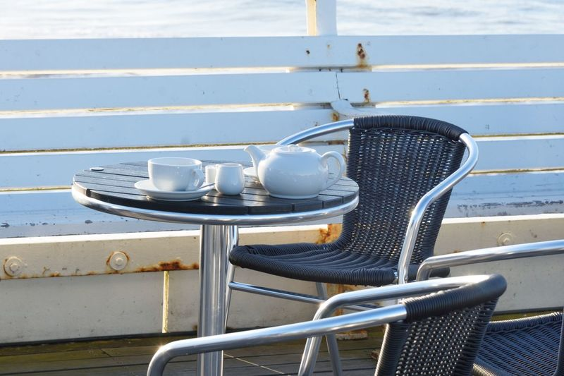 Empty Teapot and cups by the sea Chair Seat Water No People Absence Table Outdoors Empty Cup Cafe Close-up Sea Side Tea Pot Cups Tea Pots & Cups